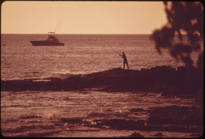 a man standing on a rocky outcropping casting a fishing line into the ocean